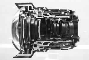 Sección transversal del impresionante esquema óptico-mecánico de 16 elementos en 11 grupos del zoom angular extremo Canon EF 11-24 mm f/4L USM, que ha supuesto un antes y un después en el diseño y construcción de este tipo de objetivos de focal variable al haber ampliado el rango ultra angular hasta los 11 mm, superando incluso la barrera de los 12 mm del super gran angular no retrofoco Voigtlander Heliar 12 mm f/5.6, lo cual puede calificarse sin ambages como hazaña, ya que el zoom de Canon es un diseño retrofoco creado para su uso con cámaras profesionales reflex full frame y en el que la lente frontal bulbosa de gran tamaño (nada menos que 108 mm) se mueve al enfocar, con una distancia mínima de enfoque que cambia según la focal utilizada: 32 cm en la posición 11 mm y 28 cm en la de 24 mm.
